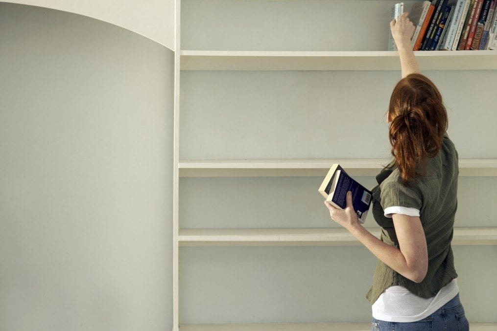 woman decluttering shelf