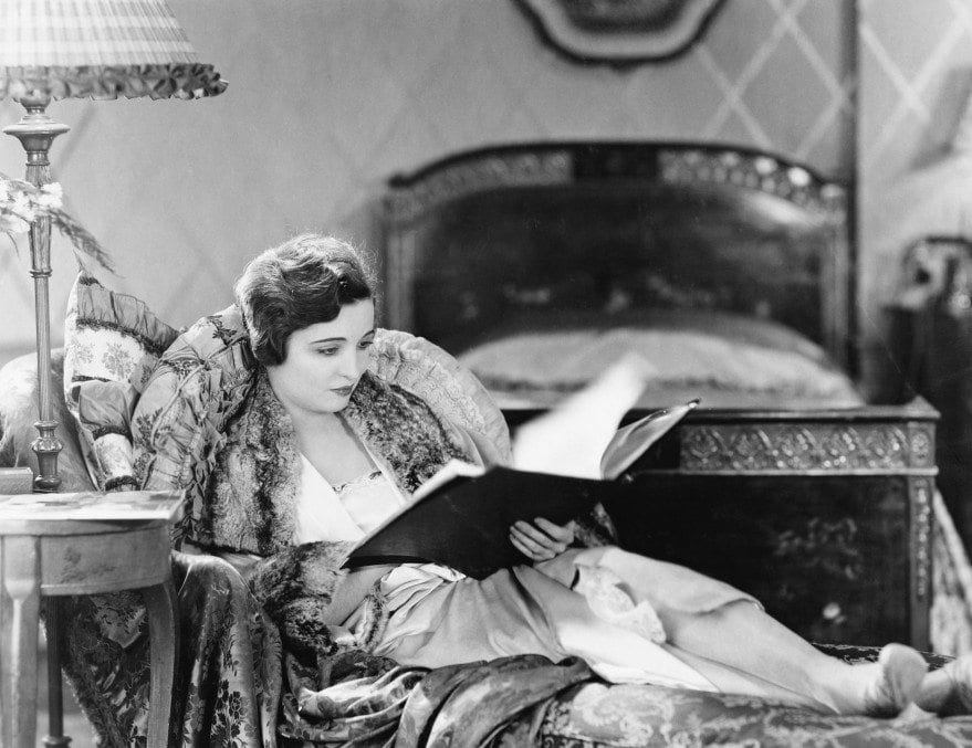 Young Woman Reclining In An Armchair And Reading A Book In Her Bed Room