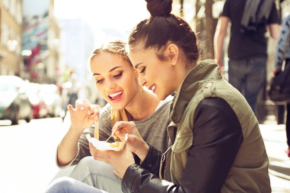 Two women eating junk food