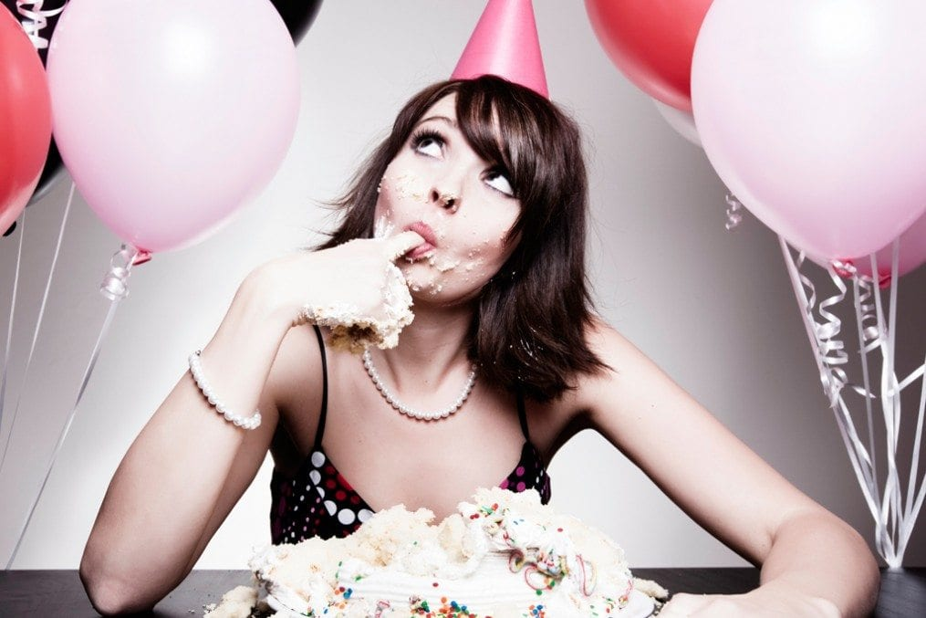 Woman eating birthday cake with hands