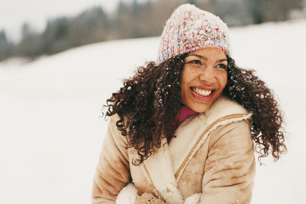 Woman smiling surrounded by snow