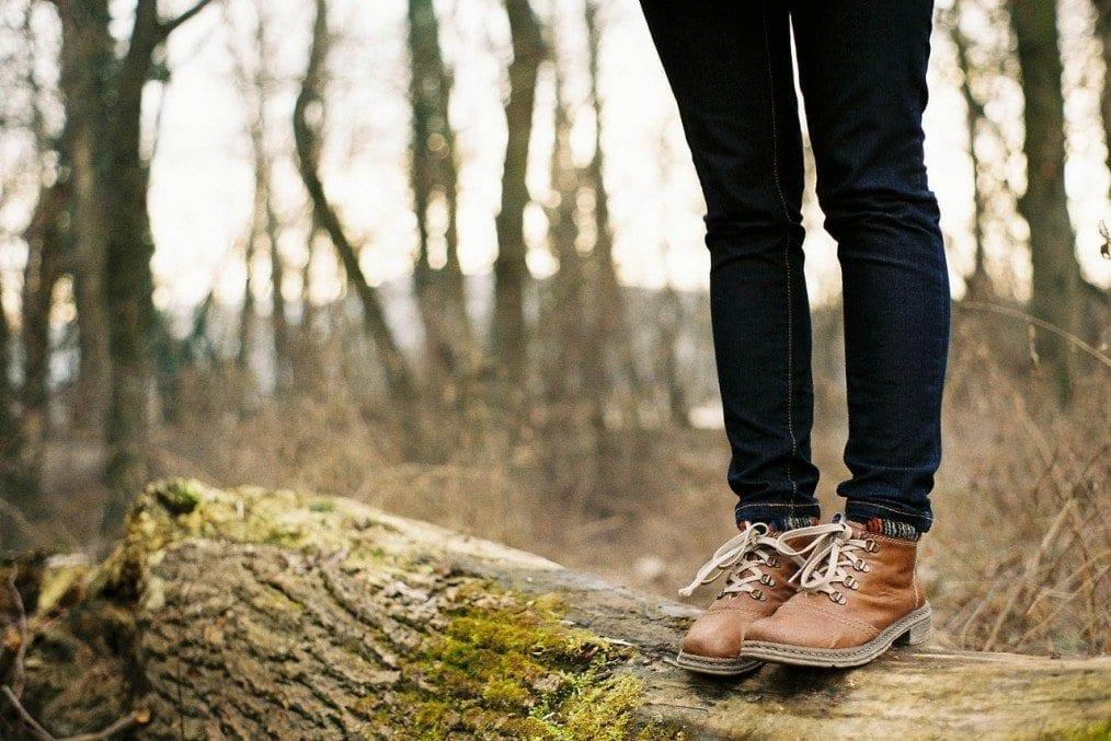 woman standing on tree log