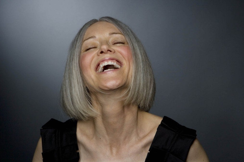Mature woman laughing, eyes closed