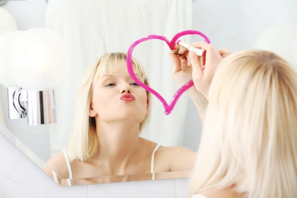 blonde woman drawing love heart in mirror with lipstick