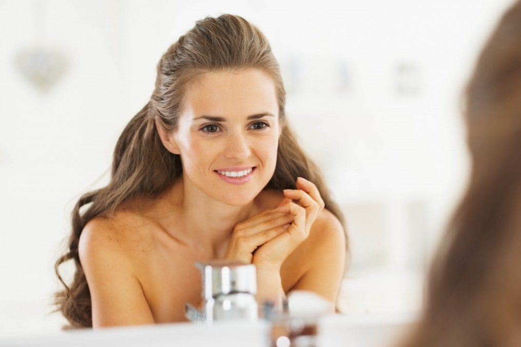 Woman with nice skin in front of mirror