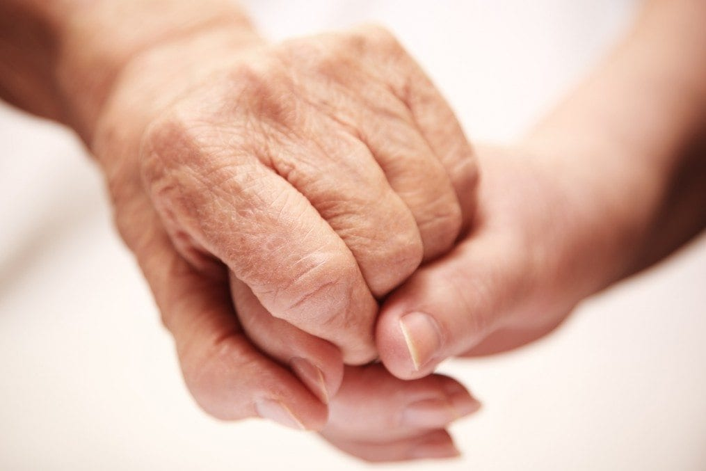 adult helping senior with dementia