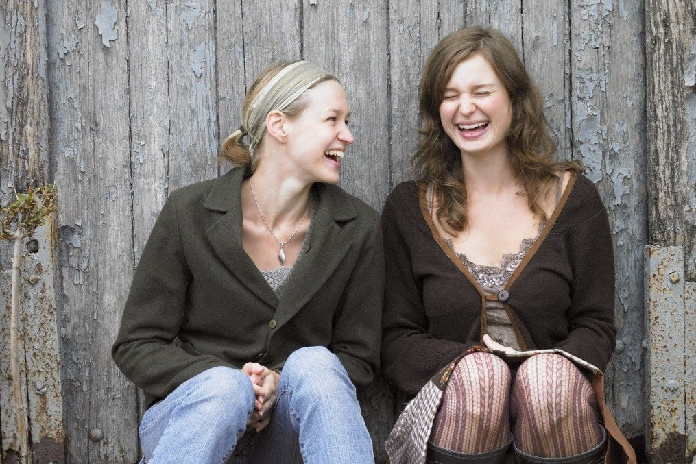 Two young women sitting by fence, laughing