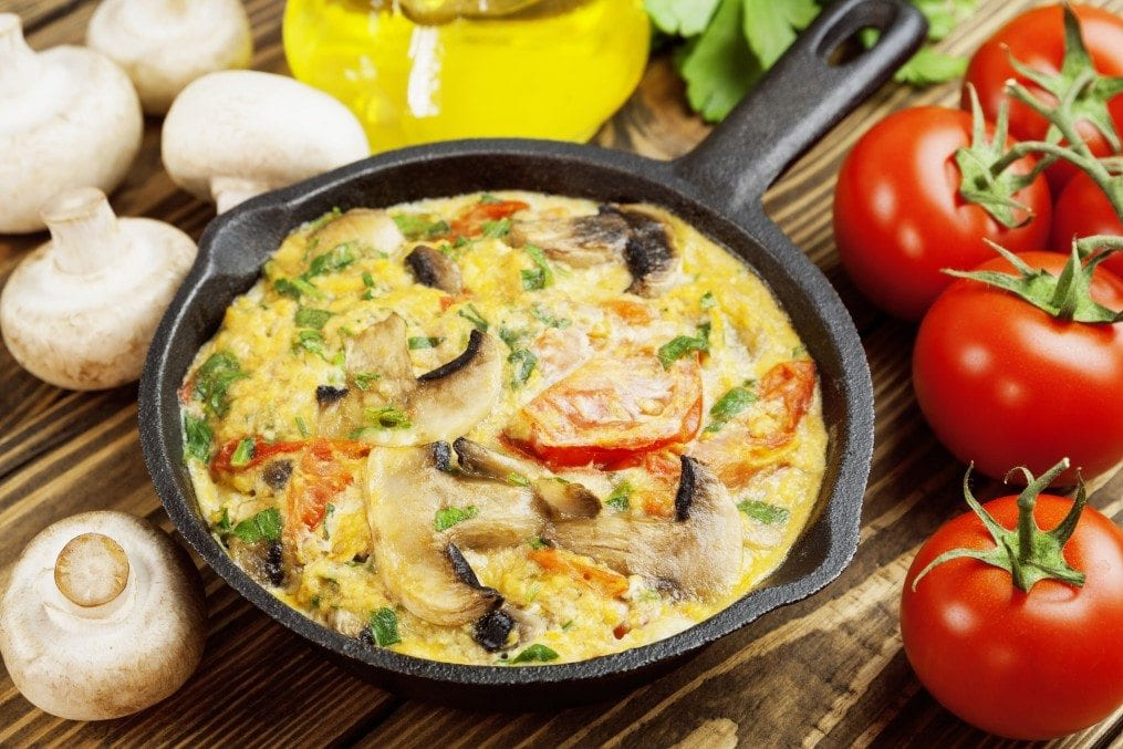 Omelet with mushrooms and tomatoes. Frittata in a frying pan