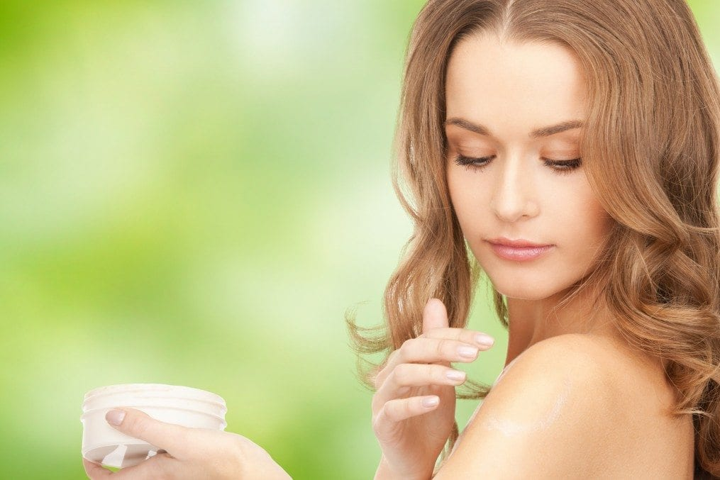 Woman applying organic cream on shoulder