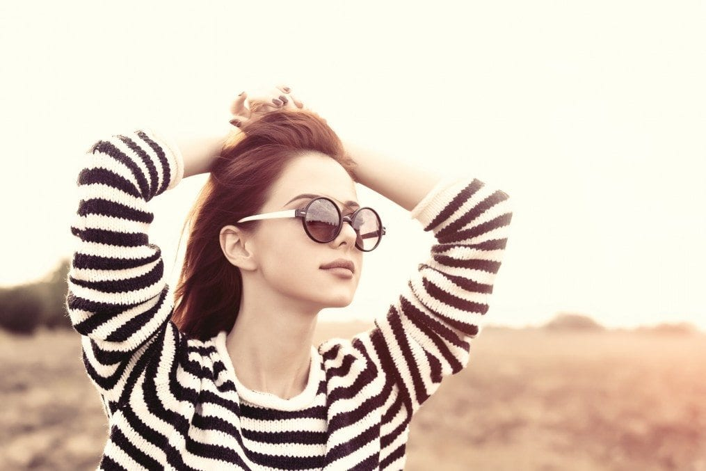 Young woman wearing shades with hands on head