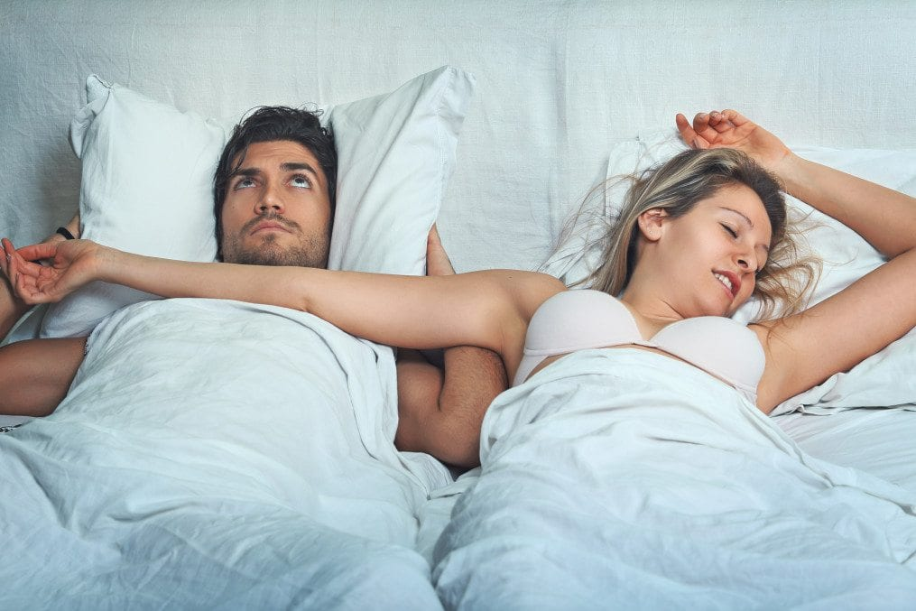 Woman snoring next to her partner in bed