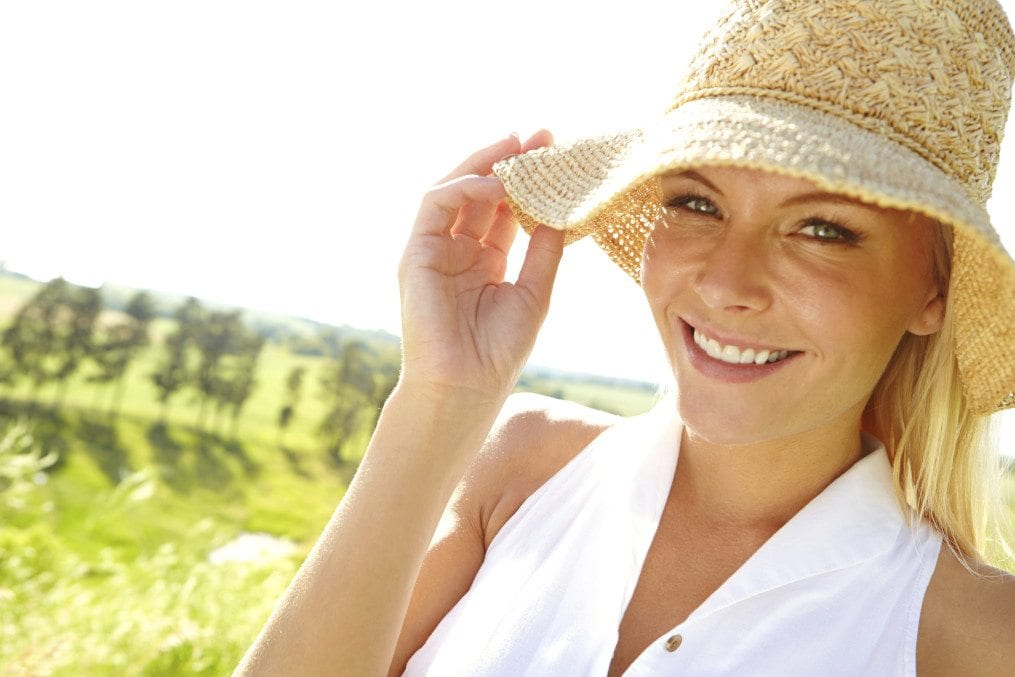 A lovely young woman wearing a sunhat smiling at the camera as she stands in the countryside