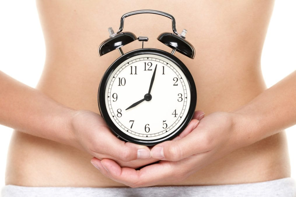 woman holding alarm clock in front of stomach