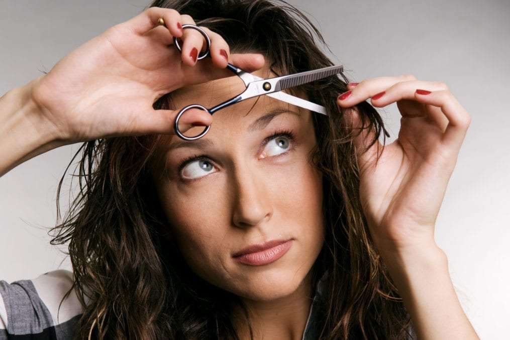 woman trimming hair with scissors