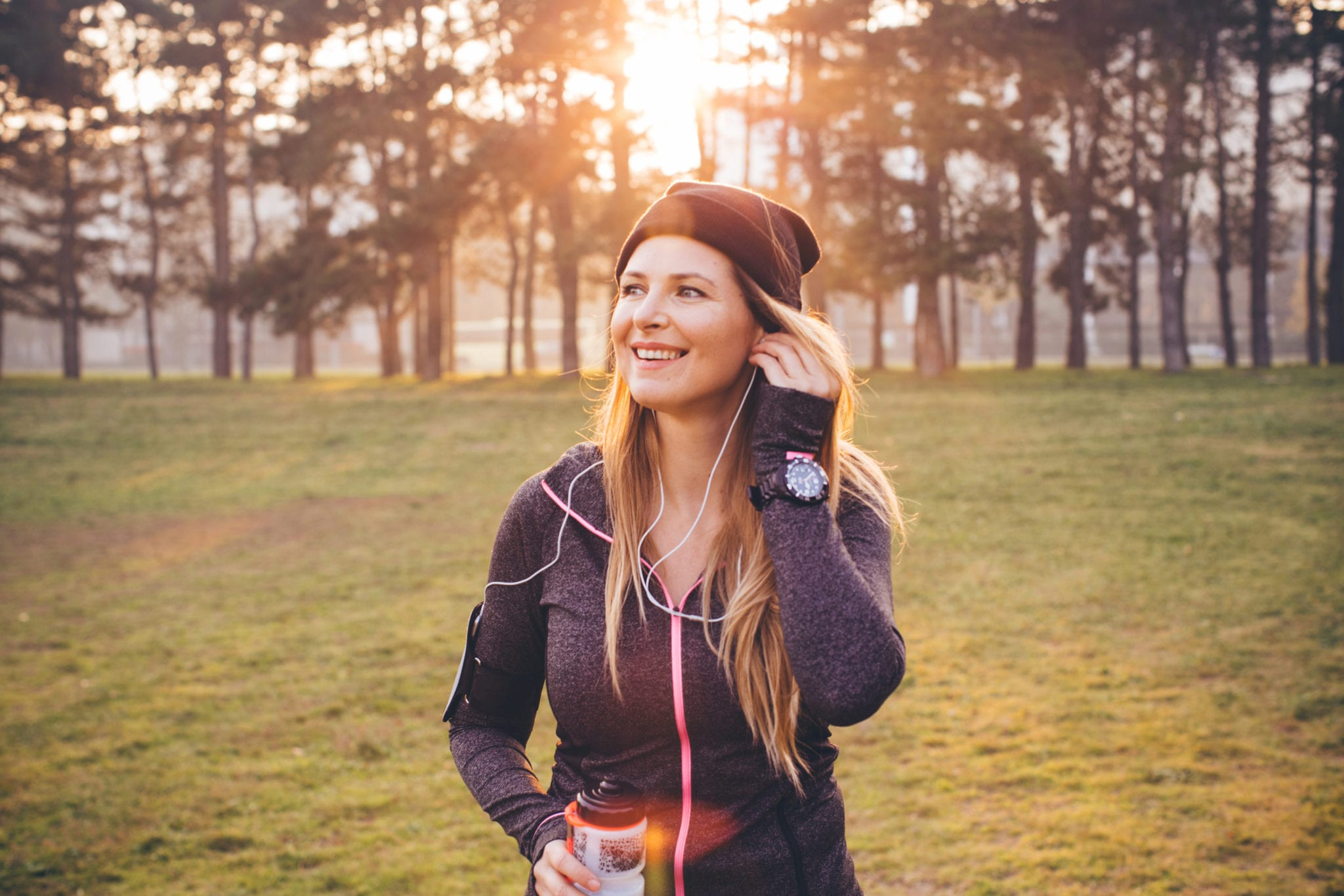 Young woman jogging outside in sunny autumn forest. She took a break to set up smartphone to monitor her progress or set up music and drink water. The sun is shining in the background .