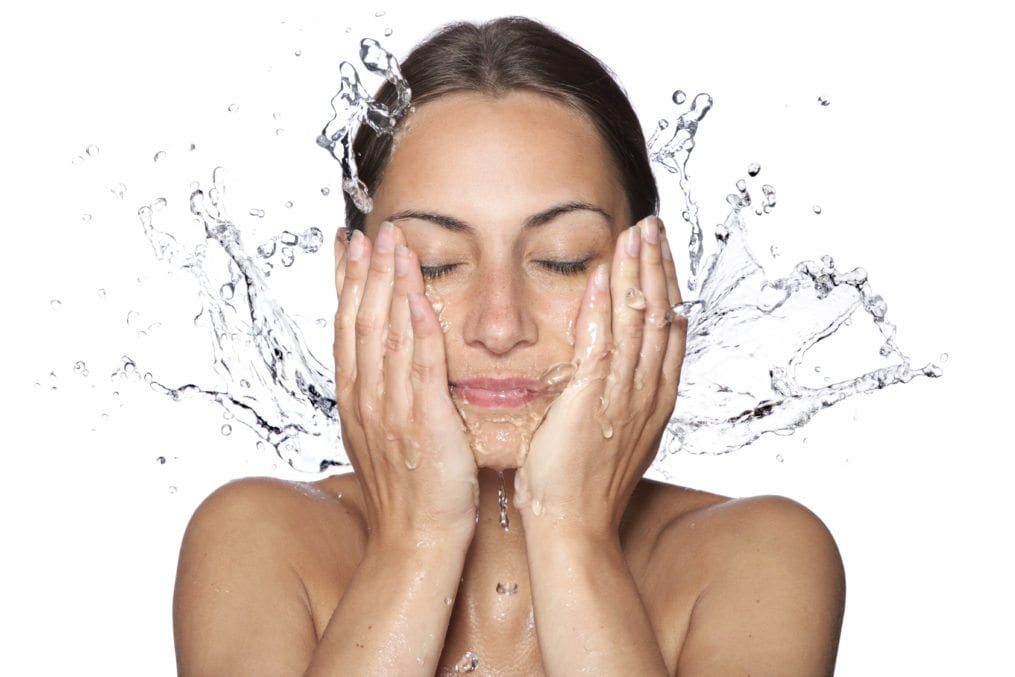 Woman splashing water on face