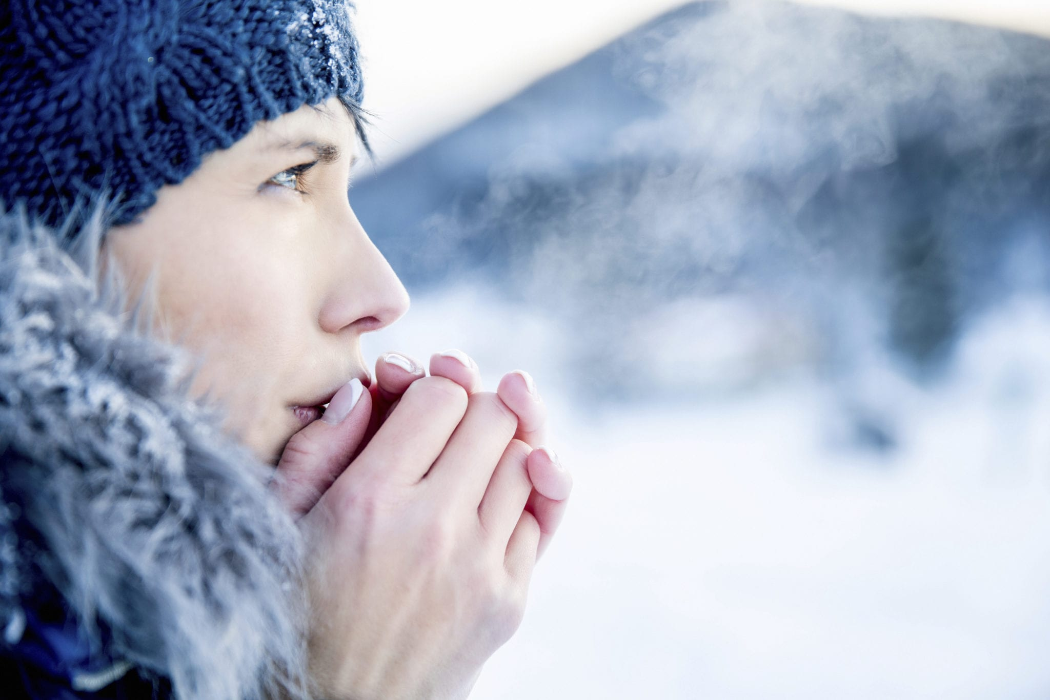 Young woman portrait on a cold winter day. Overcast and cold weather. She is heating her hands with her hot breath.