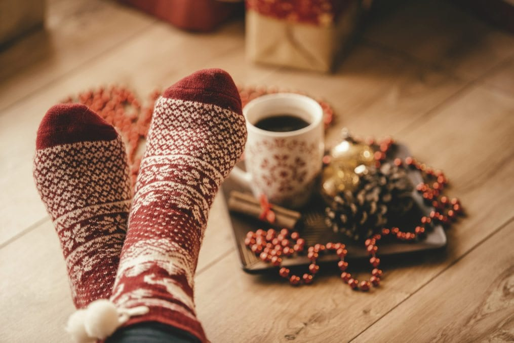 Crossed legs in seasonal winter socks, woman relaxing on Christmas day.
