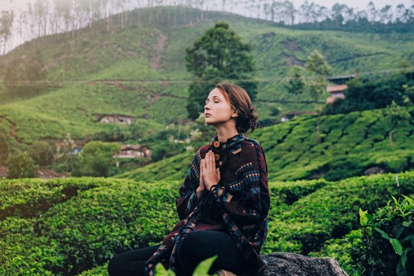 Woman meditating in green field