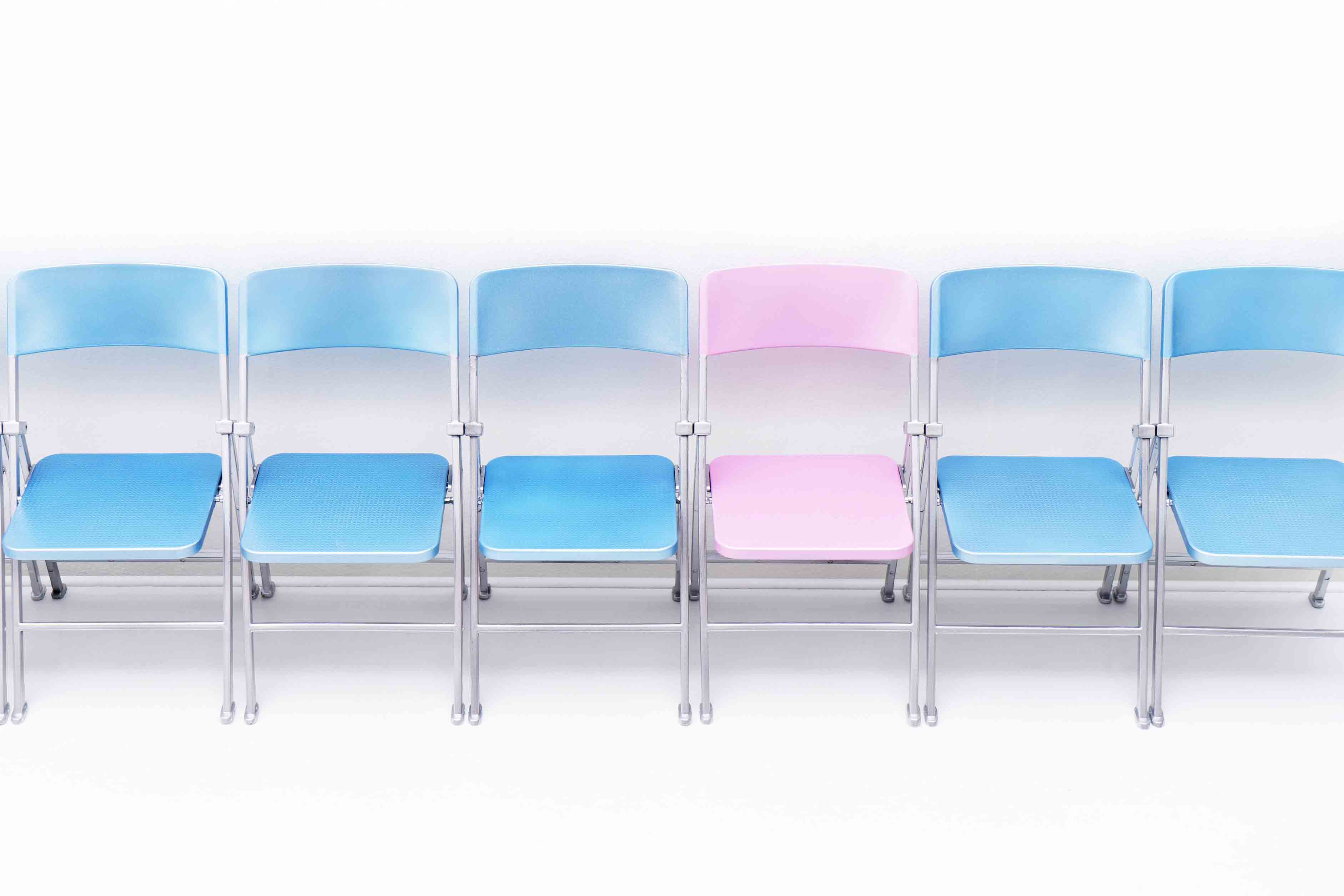 679-08718348 © Masterfile Royalty-Free Model Release: No Property Release: No One pink chair in a row of blue chairs.