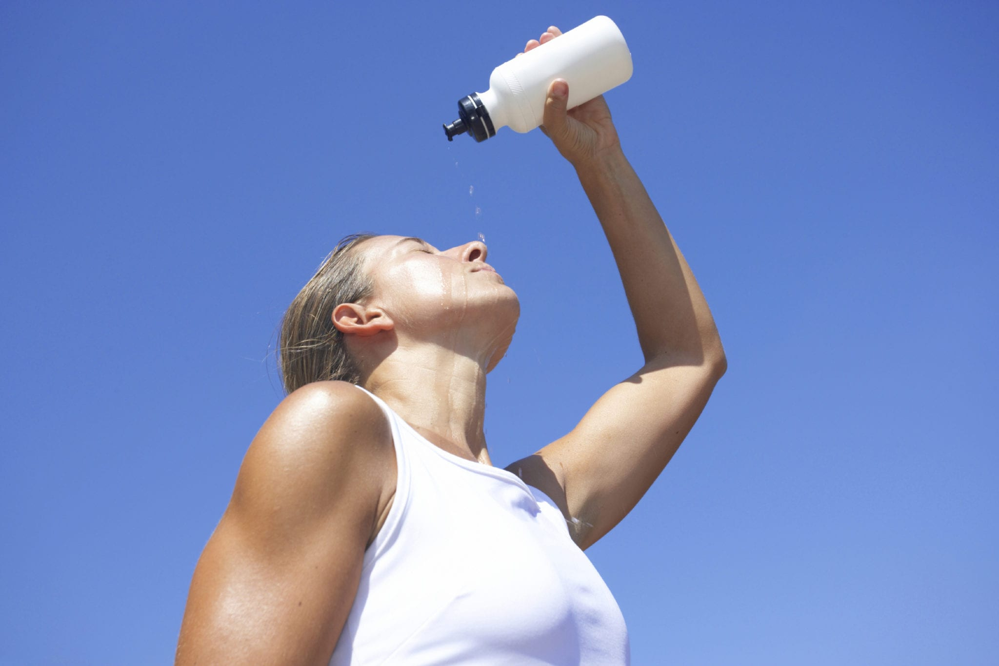 young exhausted athlete pouring water out of bottle