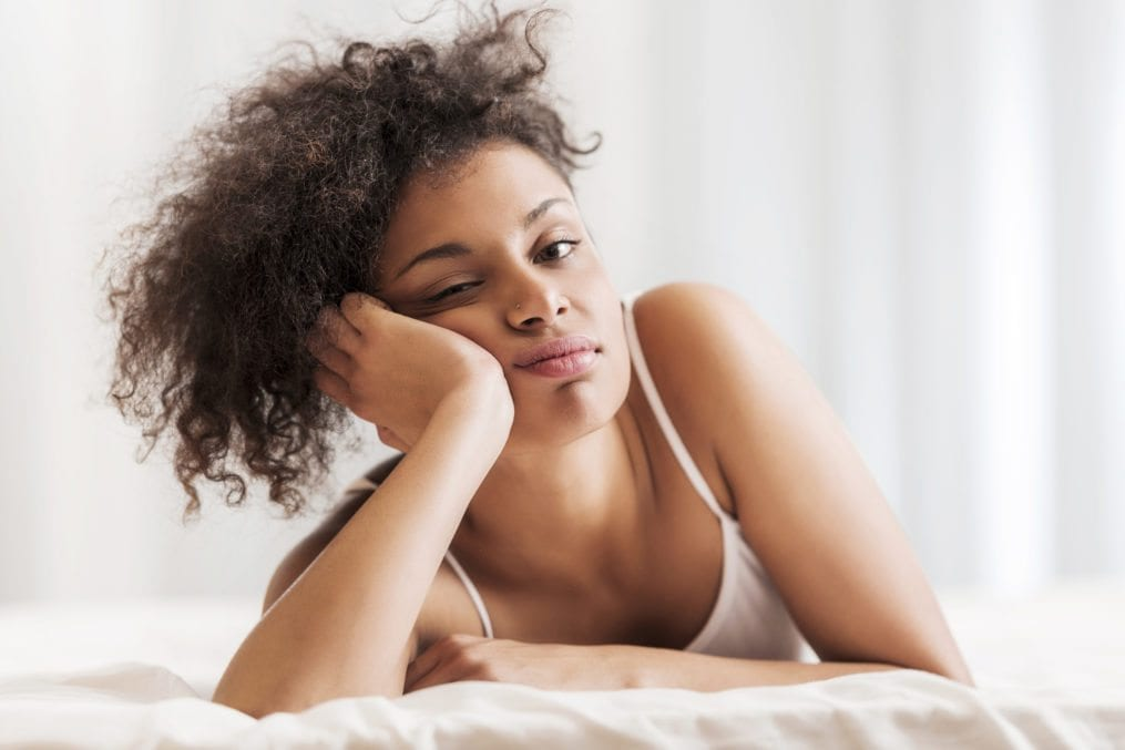 Beautiful bored African American woman lying in bed room and looking at camera.