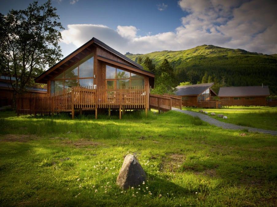 Cabin in woods near mountain grassy sunny summer