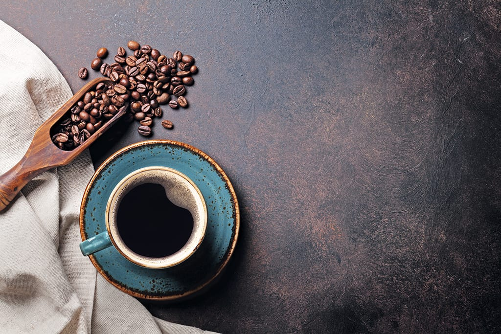 cup of coffee alongside coffee beans