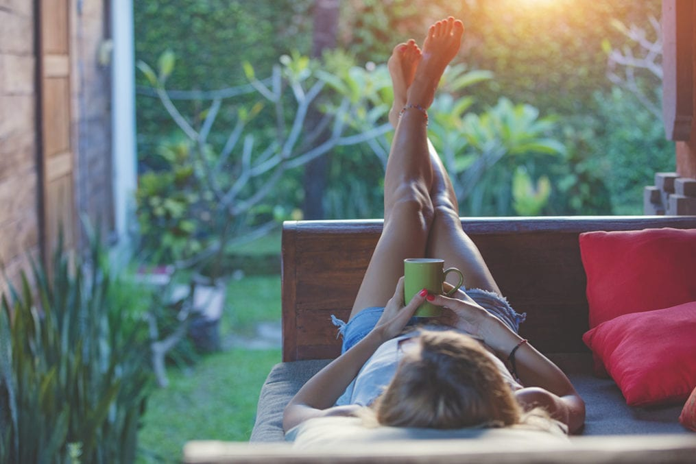 Girl enjoying early morning coffee on the garden sofa.