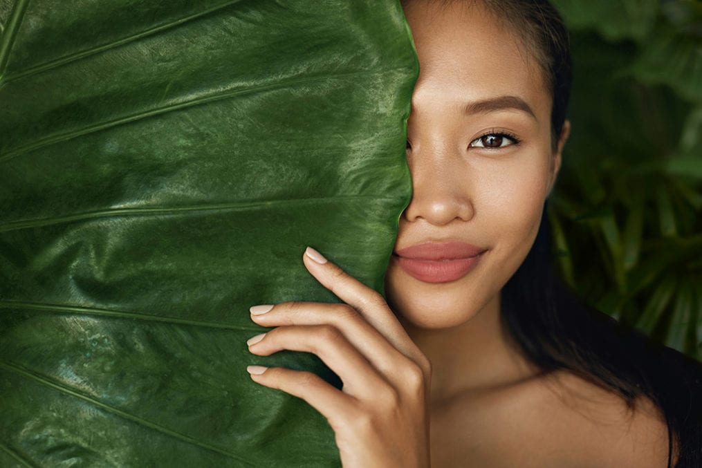 Woman model with natural makeup and healthy skin behind green leaf plant