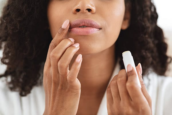 Woman applying moisturising chapstick on lips