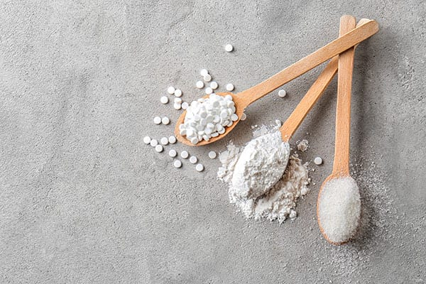 Wooden spoons with stevia pills, powdered and white sugar on grey table