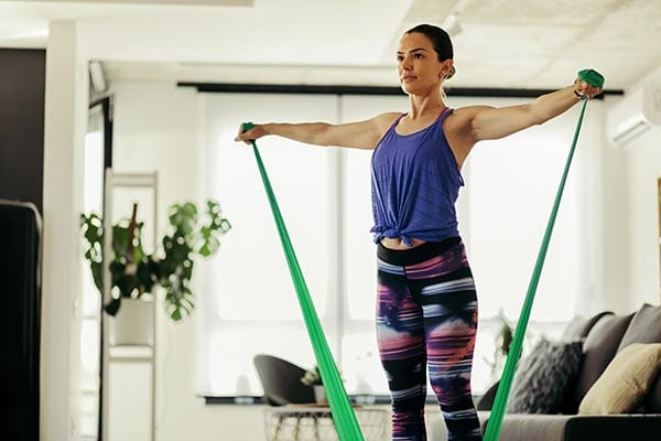 Athletic woman exercising with a power band at home.