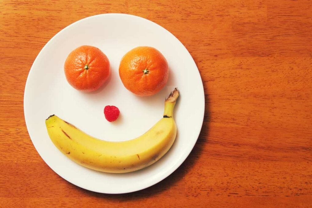 banana, oranges and a cherry on a plate