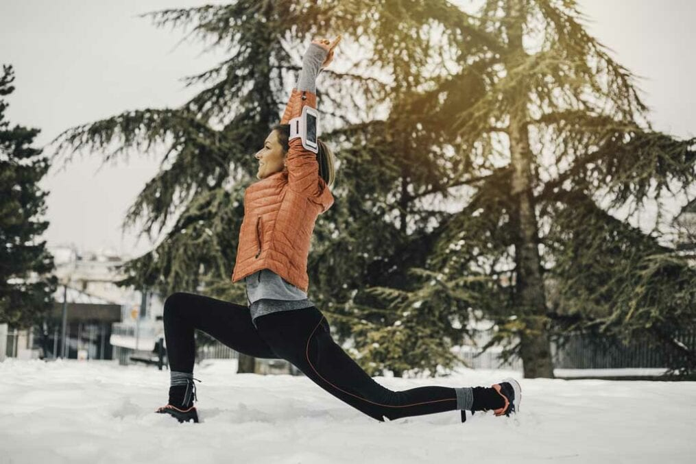 Woman stretching in the snow