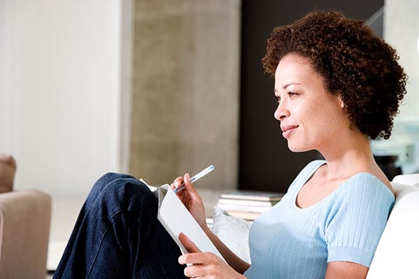Woman on couch writing a list