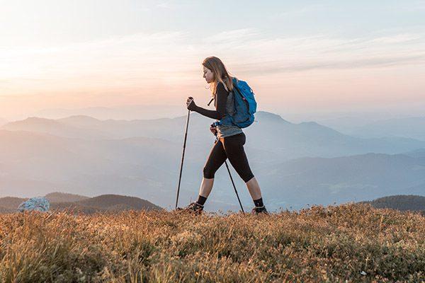 Woman hiking with poles across mountainous scenery